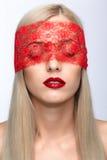 La cara de la mujer con los ojos se cerró por la cinta roja Foto de archivo