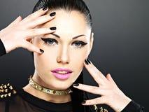La cara de la mujer de la moda con los clavos negros y brillantes hermosos hacen Fotos de archivo libres de regalías