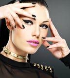 La cara de la mujer de la moda con los clavos negros y brillantes hermosos hacen Fotos de archivo