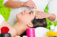 La cara de la mujer del primer que recibe el pelo facial que encera el tratamiento, la mano usando el palillo de madera para apli Imagen de archivo