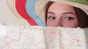 La cara de la mujer detrás de un mapa almacen de metraje de vídeo