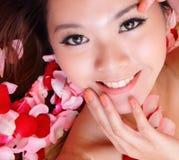 La cara de la sonrisa y del tacto de la muchacha con rojo se levantó Foto de archivo libre de regalías