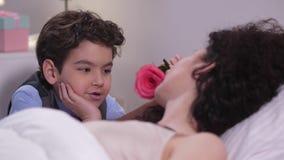 La cara de la mamá durmiente de caricia del muchacho con la rosa almacen de video