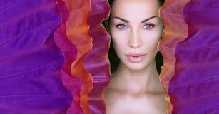 La cara de la mujer rodeada por el marco colorido ultravioleta Cara hermosa de la mujer con maquillaje natural en una hoja de neó imagenes de archivo