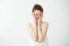 La cara de ocultación agujereada de la muchacha bonita joven cansada detrás entrega el fondo blanco Imagen de archivo libre de regalías