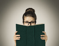 La cara de ocultación del libro abierto, mujer observa la lectura en vidrios en gris Imágenes de archivo libres de regalías