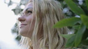 La cara de una chica joven rodeada por las hojas almacen de video