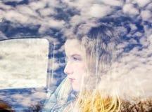 La cara de una muchacha adolescente y de nubes reflejó en una ventana del camión Imagenes de archivo