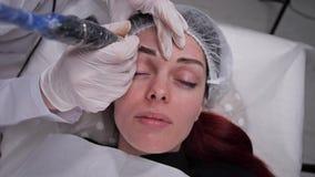 La cara de una muchacha que hace maquillaje permanente de la ceja 4K MES lento almacen de video