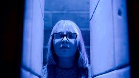 La cara de una mujer está iluminada con la luz coloreada La muchacha mira misterioso la cámara almacen de metraje de vídeo