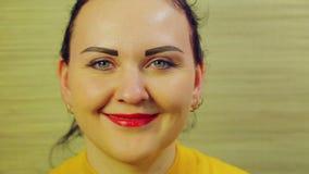 La cara de una mujer expresa las emociones de la alegría y del positivo Para arriba aumentado dedo índice metrajes