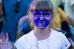 La cara de una niña en pinturas azules del holi Imágenes de archivo libres de regalías