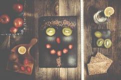La cara divertida arregló de la linaza, del kiwi y de la fresa en s negro imagen de archivo libre de regalías