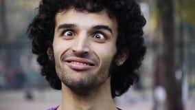 La cara divertida del hombre joven que bizqueaba la posición oblicua observó el ojo almacen de metraje de vídeo