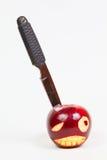La cara enojada se talla en una manzana y un cuchillo Fotografía de archivo