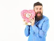 La cara feliz del hombre barbudo hermoso lleva a cabo el corazón de las tarjetas del día de San Valentín Fotografía de archivo