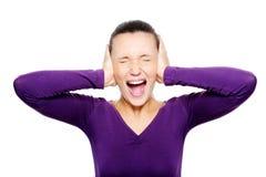 La cara femenina de griterío exprime sus oídos a mano Imagen de archivo libre de regalías