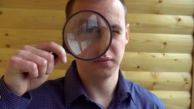 La cara grande de un hombre curioso que mira la cámara con una lente que magnifica un detective privado detective metrajes