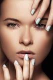 La cara hermosa de la mujer con los clavos azules manicure, piel limpia Foto de archivo