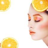 La cara hermosa joven de la mujer con la naranja compone Fotos de archivo