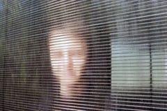 La cara joven sonriente borrosa detr?s de Dusty Fluted o del vidrio acanalado, policarbonato claro acanal? la hoja En l?nea an?ni imagen de archivo