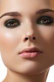 La cara modelo, forma maquillaje ahumado del ojo y limpia la piel fotografía de archivo libre de regalías