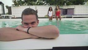 La cara sonriente del individuo joven mojado getted hacia fuera de la piscina al aire libre en el fondo de dos muchachas hermosas almacen de video