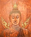 La cara y la pista de Buddha tallaron en la teca fotografía de archivo libre de regalías