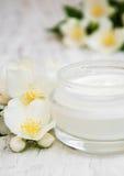 La cara y las cremas hidratantes de la crema corporal con el jazmín florece Imagen de archivo libre de regalías