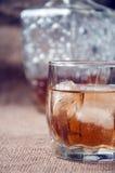 La carafe et le verre de whiskey, bourbon de whiskey sur une toile de jute, renvoie le fond Image stock