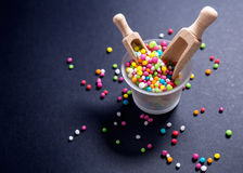 La caramella colorata, lo zucchero imperla con il mestolo di legno su fondo nero Immagine Stock