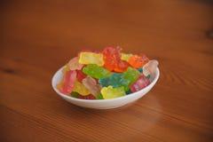 La caramella della gelatina riguarda il fondo di legno Candy riguarda una ciotola Mucchio degli orsi della caramella della gelati Fotografia Stock