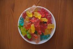 La caramella della gelatina riguarda il fondo di legno Candy riguarda una ciotola Mucchio degli orsi della caramella della gelati Immagini Stock
