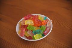 La caramella della gelatina riguarda il fondo di legno Candy riguarda una ciotola Mucchio degli orsi della caramella della gelati Fotografia Stock Libera da Diritti