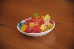 La caramella della gelatina riguarda il fondo di legno Candy riguarda una ciotola Mucchio degli orsi della caramella della gelati Fotografie Stock Libere da Diritti