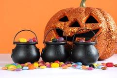 La caramella felice di Halloween nello scherzetto o dolcetto porta i calderoni con la zucca Immagini Stock