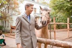 La caresse belle de jeune homme un cheval brun clair dans la ferme Images libres de droits