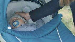 La caricia de la mano del ` s de la madre su hijo en el cochecito de niño metrajes