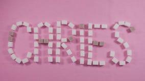 La carie di parola è allineata con i cubi dello zucchero raffinato su un fondo rosa Concetto della carie stock footage