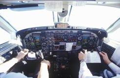 La carlinga y los pilotos en un aeroplano del viajero Imágenes de archivo libres de regalías