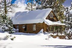 La carlingue de montagne avec la neige a couvert le toit Photos stock