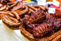 La carne ahumada y las salchichas en cestas de mimbre vendieron en el mercado Imagen de archivo libre de regalías