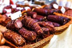 La carne ahumada y las salchichas en cestas de mimbre vendieron en el mercado Imágenes de archivo libres de regalías