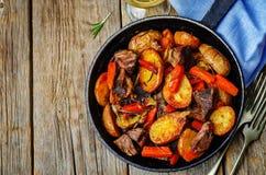 La carne asó con las patatas, las zanahorias, las cebollas, el romero y el ajo imagen de archivo libre de regalías