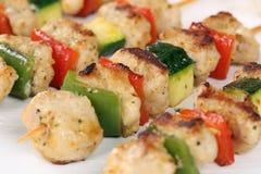 La carne asada a la parrilla del pollo ensarta la comida con las verduras Foto de archivo