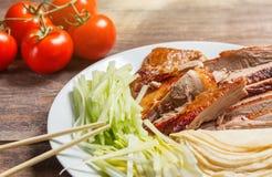 La carne china del pato de Pekín sirvió con las cebollas, crepes, pedazos del pepino y los tomates en la placa blanca con los pal Fotos de archivo libres de regalías