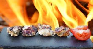 La carne cocinada miente en una piedra negra Foto de archivo