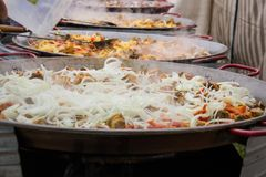 La carne con la cipolla è fritta in padelle enormi che stanno in una fila Preparazione di alimento collettivo Fotografia Stock
