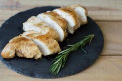 La carne cortada del pollo sirvió en la placa de la pizarra con romero fresco Fotos de archivo libres de regalías