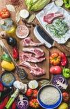 La carne cruda cruda dell'agnello taglia, riso, petrolio, spezie e verdure Immagini Stock